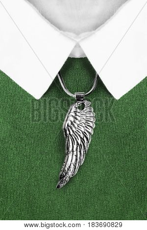 Silver wing pendant over green pullover with white collar closeup