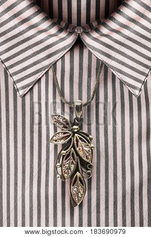 Vintage gold enameled pendant over satin striped blouse closeup