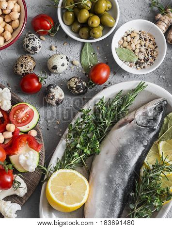 Mediterranean style food. Fish vegetables herbs chickpeas olives cheese on grey background top view. Healthy food concept. Flat lay