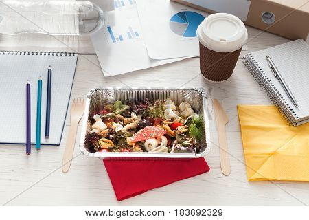 Healthy business lunch in the office, coffee take away cup and vegetable salad in foil container on white wooden desk. Snack at break time