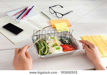 Healthy business lunch in the office, pov view of eating person. Vegetables with parmesan plate on white wooden desk near mobile phone and open organizer. Snack at break time
