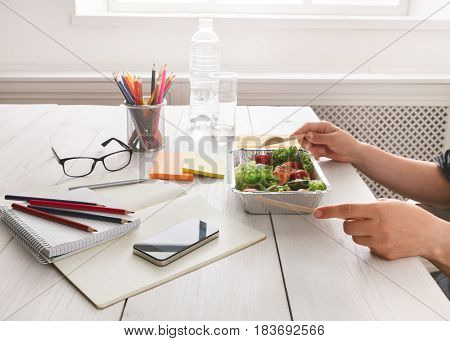Healthy business lunch in the office, side view of eating person. Salad plate with salmon on white wooden desk near mobile phone and open organizer. Snack at break time