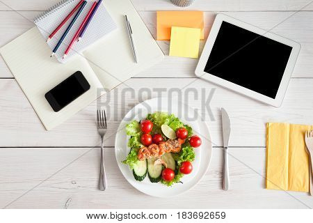 Healthy business lunch in the office, top view of dish on white wooden desk near tablet, mobile phone and open organizer. Salad plate with salmon. Snack at break time
