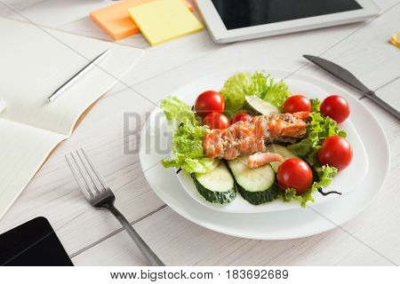Healthy business lunch in the office, dish on white wooden desk near tablet and open organizer. Salad plate with salmon. Snack at break time