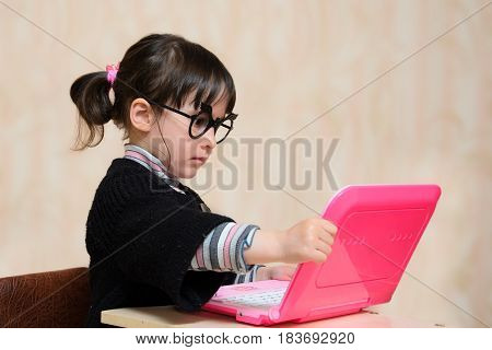 Child in glasses and old clothes is sitting at the laptop.