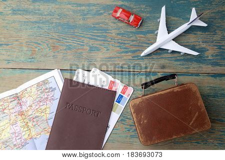 Preparation for Traveling concept. Money, passport, airplane, suitcase and map on a vintage wooden background with copy space.