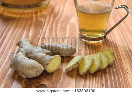 Ginger tea with ginger sliced on a wood table