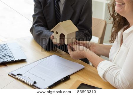 Hands Giving House Model To Other Hands With Agreement On Desk. House Representing Home Ownership On