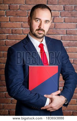 Businessman Clasps A Folder To His Chest