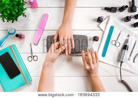 Closeup shot of a woman in a nail salon receiving a manicure by a beautician with nail file. Woman getting nail manicure. Beautician file nails to a customer.