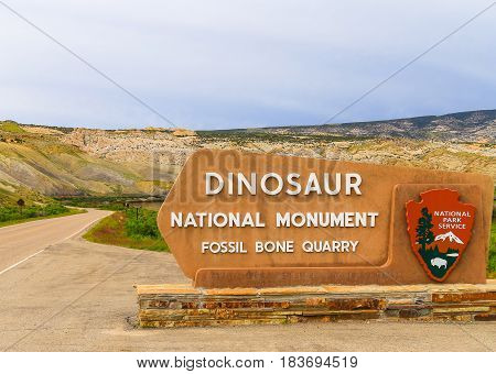 JENSEN USA - MAY 29 2016: Entrance sign of the Dinosaur National Monument and the quarry that contains dinosaur fossils.