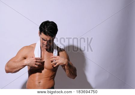 The sexy man is toweling off his body.