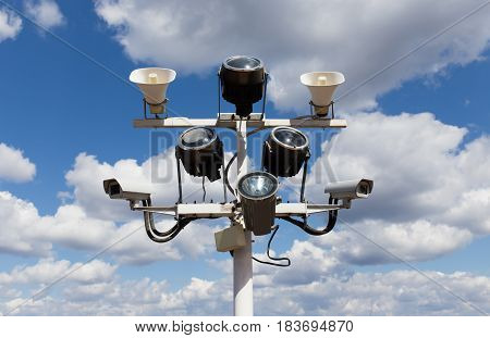 Two security camera floodlights and loudspeakers on blue sky background