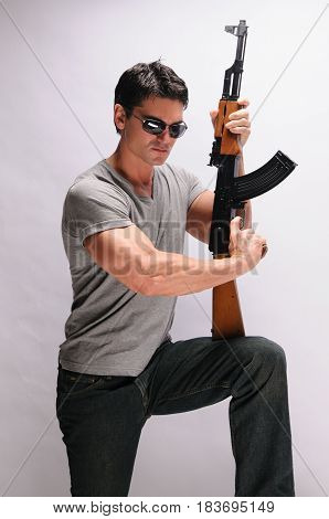 The divine sexy man is holding his rifle.