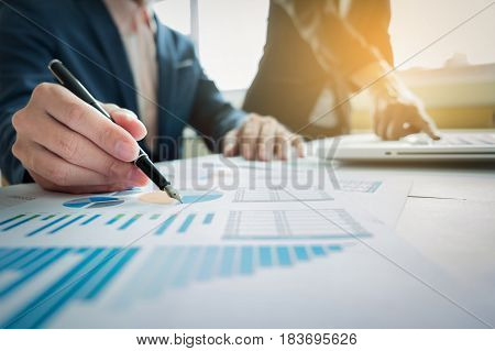 Business team working at office with laptop and financial graph data documents on his desk