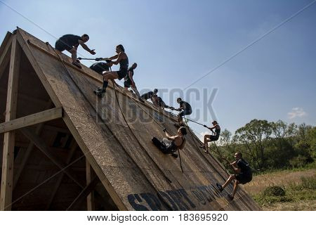Team Of Men And Women Climbing With Ropes On A Wall