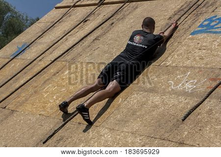 A Man Climbing With A Rope On A Wall