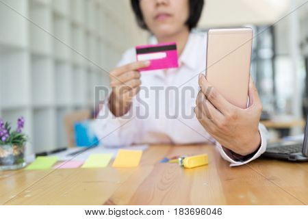 Woman's Hands Holding A Credit Card For Payment And Using Smart Phone For Online Shopping