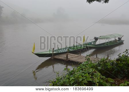long tail motor boat mooring near quayside with morning mist