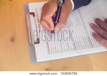 Hand Fill Out Mortgage Loan Application On A Clipboard. A Form To Be Filled By A Homeowner Who Want