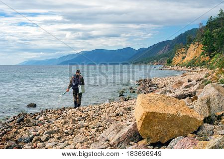 The fisherman walks along the shore of  a large lake with fishing tackle