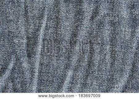 Close up view of wrinkles and pale stripes on a denim cotton cloth. Textured background for several creative design.