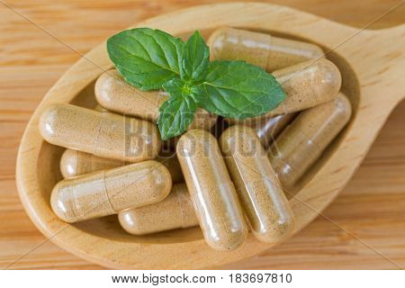 Macro of wooden spoon full of herbal medicine in clear capsules, ideal for Homeopathic remedies on wood background