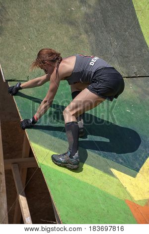 A Woman Is Climbing A Wall In A Strength Race