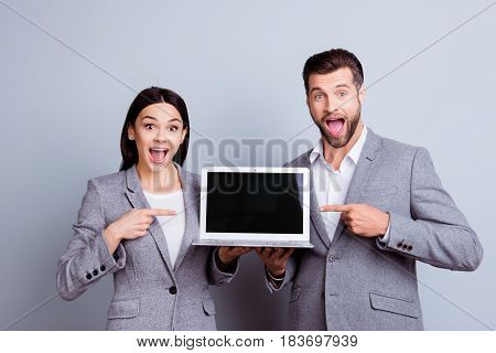 Two People In Formal Clothing Holding Laptop With Black Screen And Pointing On It With Their Finders