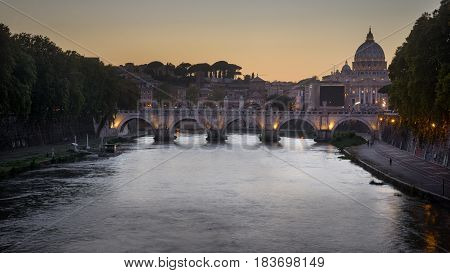 Evening illumination of ponte Sisteo and St. Peter's basilica in Rome, autumn Italy