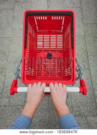 Female hands pushing empty shopping cart. Personal point of view.