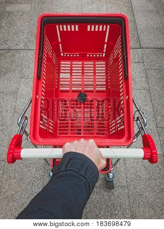 Male hand pushing empty shopping cart. Personal point of view.