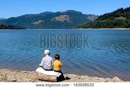 Landscape lake along mountains. two small brothers siting on the log back to frame on lake shore.Consept of  relationship, support, fishing in Romania.