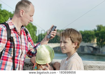 Family of three with smartphone standing at Rome bridges summer background