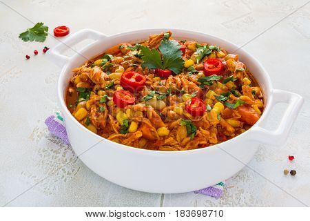 Hearty and healthy Southwest chicken and beans stew in a white casserole on the table.