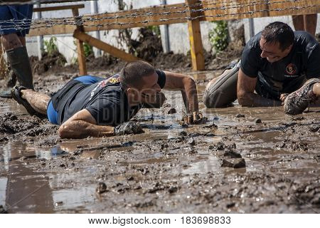 Two Men Crawling Under Barbed Wire