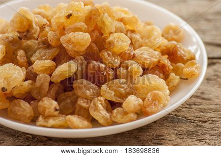 dried grapes close up on white plate on wooden background