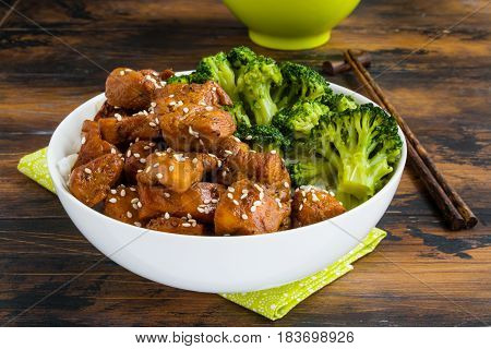 Chicken lacquered with a sweet soy teriyaki sauce in a white bowl. Garnished with rice and broccoli. Chopsticks brown wooden table.