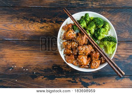 Chicken teriyaki rice and broccoli in a white big bowl with chopsticks above. Wooden rustic table top view.