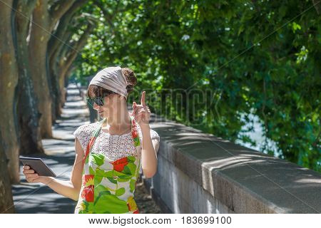 Tourist girl is looking at tablet in hand on green tree avenue