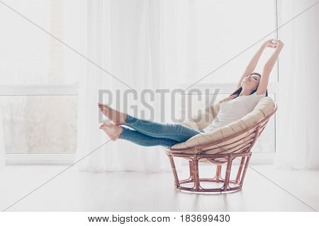 Young Girl Is Stretching In Modern Armchair In Light Livingroom. She Is Sleepy And Dreamy, Wearing C
