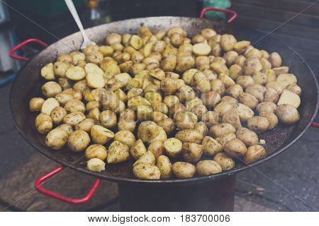 Country fair cooking. Roasted potatoes cooked outdoors in big metal cauldron pot. Cookout vegetable meals. Fresh organic, healthy snack, potatoes cooked on grill flame. Street fast food.