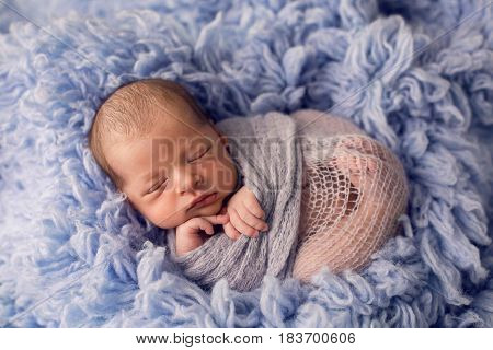 Newborn boy lies on a bed in blue fur and sleeps sweetly