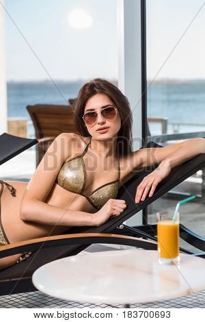 Body care. Woman with perfect body in bikini lying on the deckchair by swimming pool at resort spa hotel.