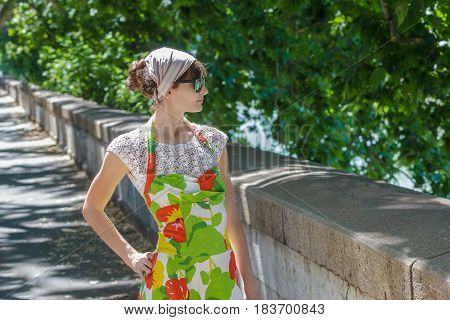 Woman in floral summer sundress is posing at green tree city alley background