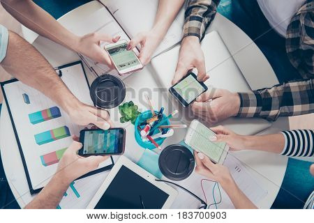 Top Up Of Four Friends Using Their Smartphones For Searching Ideas For New Successful Business In Wo