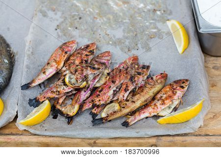 Plenty of red mullet grilled at barbecue. Seafood bbq outdoors at picnic, party. Street food vendor makes take away on big tray. Grill crispy roasted fish with lemon