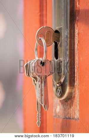 Key in keyhole on door. Rusty keys in old door lock. Selective focusing