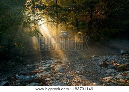 Car SUV in the sunlight making its way through the fog in the background of a mountain forest and a river. Gelendzhik Russia