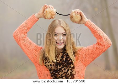 Smiling Fashion Woman In Park Holding Earmuffs.